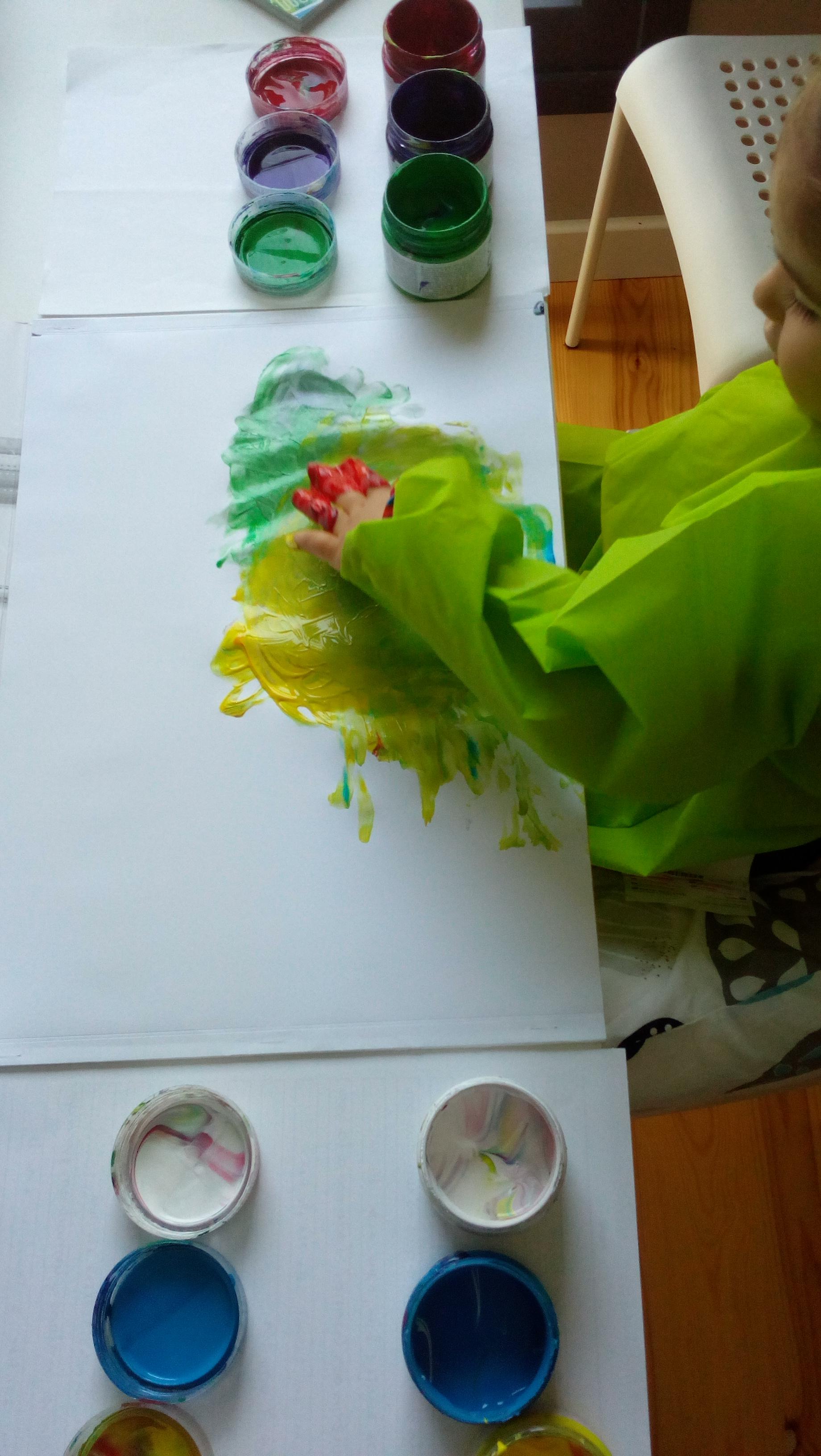 Una niña pinta con pintura de dedos.