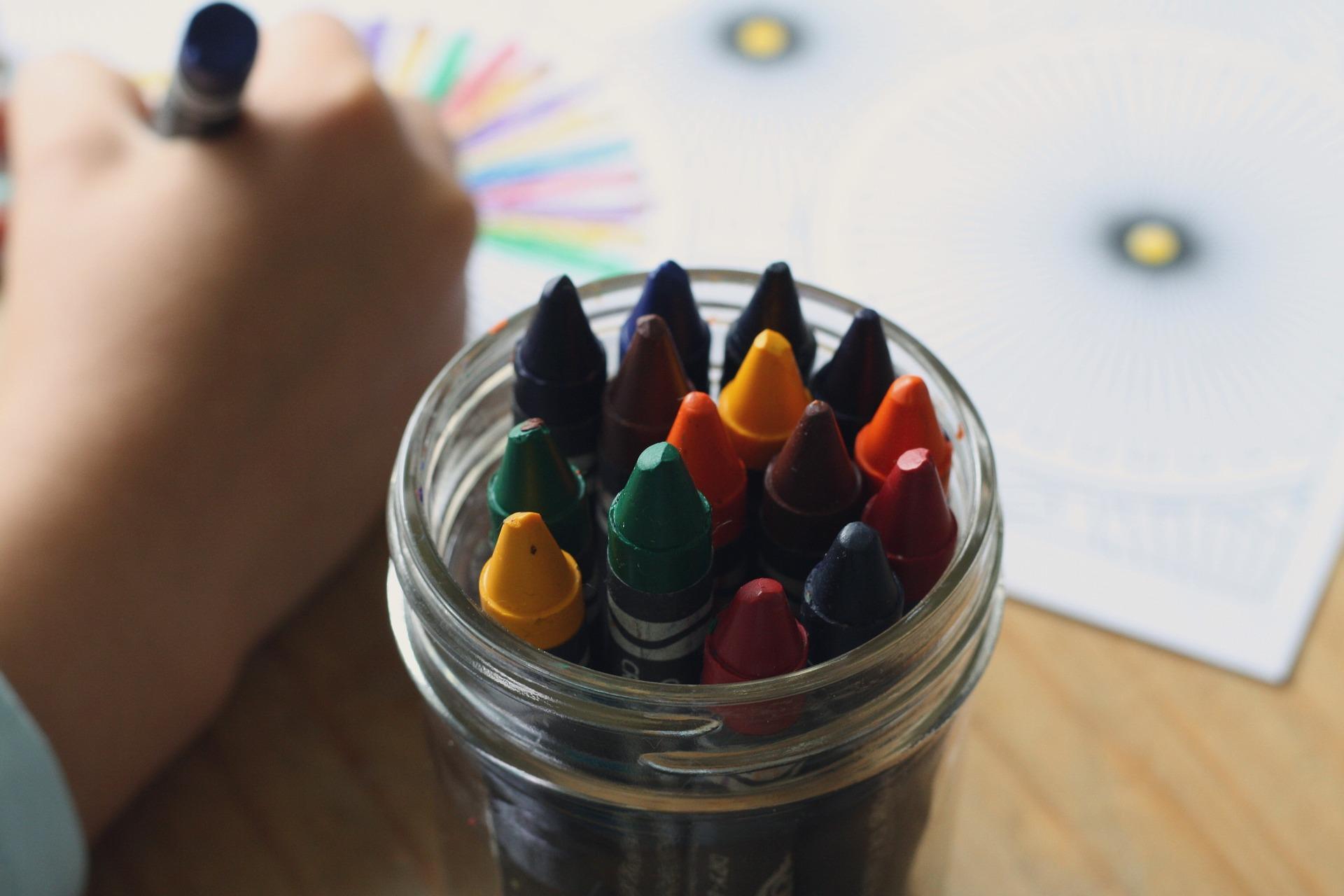 Un niño pinta con ceras de colores.